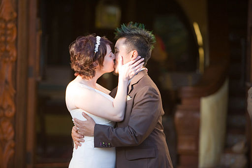 the bride and the groom kissing after the wedding ceremony