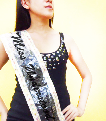 "a girl with a sash which says ""Miss understood"""