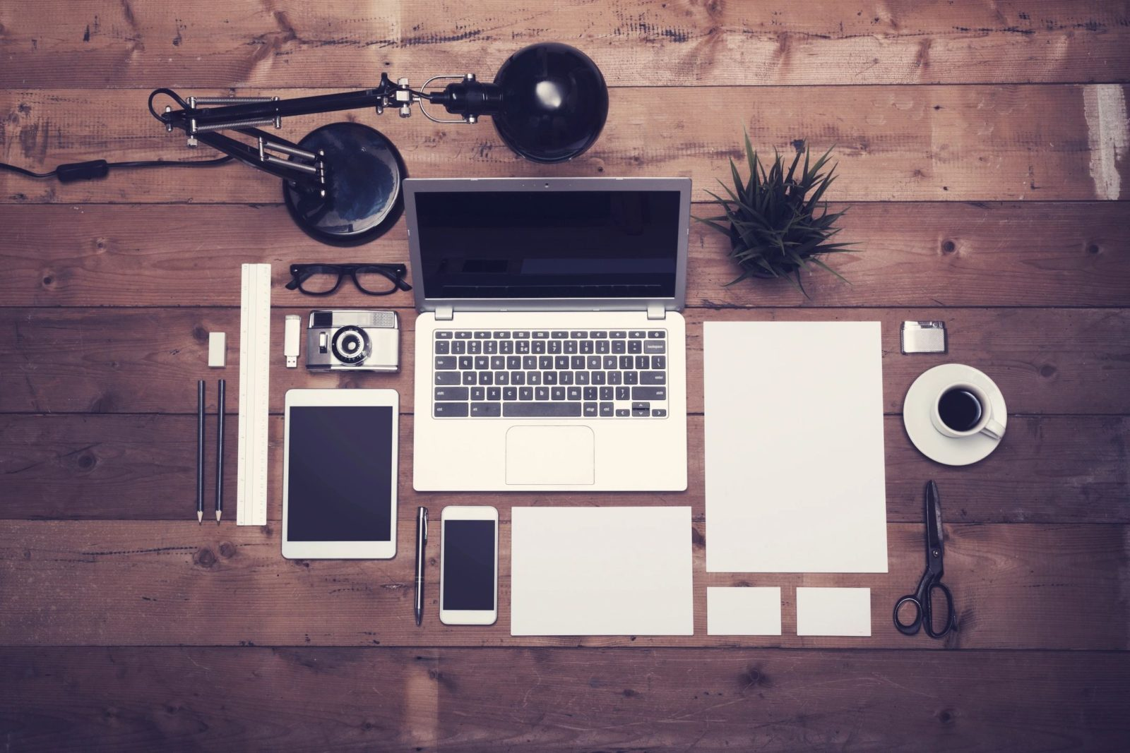 Business blogging: Gadgets on the table - laptop, tablet, smartphone, paper, ballpens, table lamp