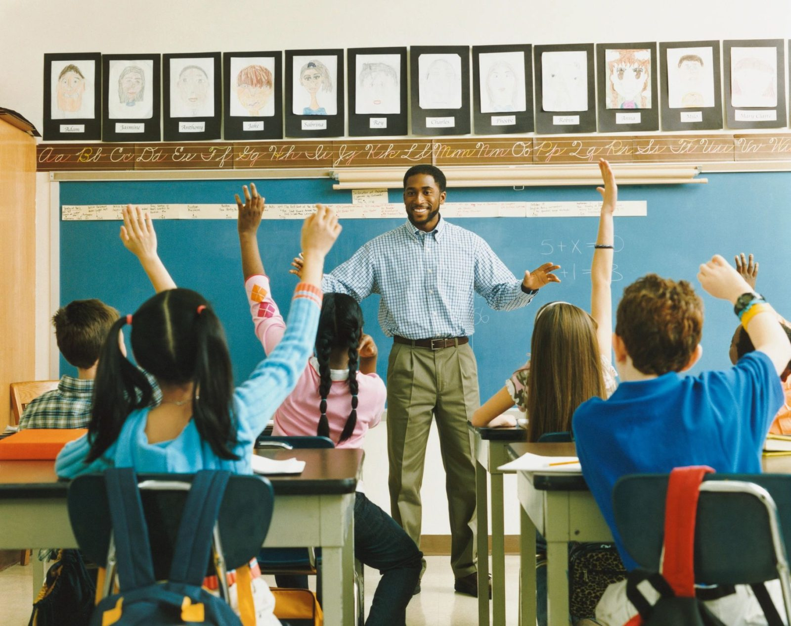 pupil raising their hands during classroom session