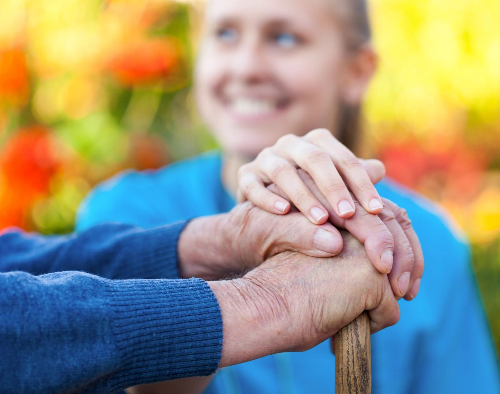 a young girl holding the hands of the elder as a show of respect